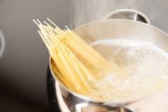 Panna med spagettimatlagning i kokande vatten Arkivfoto