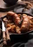 Panna med stekte potatisar och korvar, gaffel och kniv royaltyfria bilder