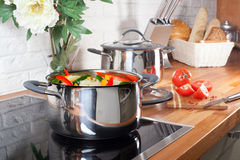 Panna på ugnen med grönsaker i kökinre Royaltyfria Bilder