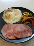 Panna stekt tillbaka bacon, över det lätta ägget och sauteed spansk pepparfrukost Royaltyfri Foto