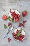 Pannakotadessert met aardbeien en rode aalbessen op uitstekende houten witte achtergrond De ruimte van het exemplaar stock afbeeldingen