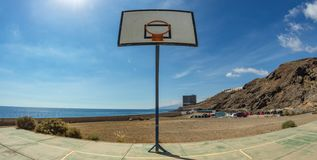 Panneau arrière de basket-ball avec le panier sur le vieux champ de sports Bâtiment abandonné énorme devant l'océan à l'arrière-p photographie stock libre de droits