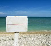 Panneau blanc de conseil sur une plage avec l'océan sur le fond pour le concept graphique Photo stock
