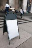 Panneau blanc vide vide de signe sur le plancher en béton devant des étapes de manière d'entrée de la construction extérieures Photographie stock