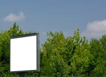 Panneau d'affichage avec le ciel bleu de l'espace blanc et les nuages, arbres Photographie stock libre de droits