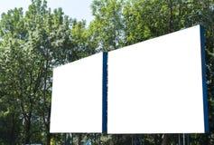 Panneau d'affichage avec le ciel bleu et les arbres de l'espace blanc Photo libre de droits