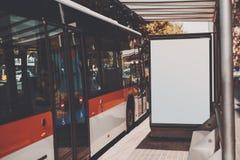 Panneau d'affichage blanc près d'autobus rouge Photos stock