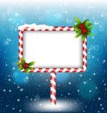 Panneau d'affichage de canne de sucrerie avec le houx en chutes de neige Image stock