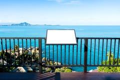 Panneau d'affichage de publicité vide sur la barrière en acier au-dessus de la mer bleue calme Image libre de droits