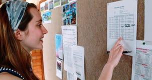 Panneau d'affichage de sourire de lecture d'écolière dans le couloir banque de vidéos