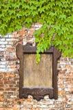 Panneau d'affichage en bois contre un mur de briques couvert dans le lierre Photographie stock libre de droits