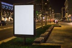 Panneau d'affichage rougeoyant vide vertical sur la rue de ville de nuit Dans les bâtiments et la route de fond avec des voitures photos libres de droits