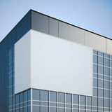 Panneau d'affichage vide accrochant sur l'immeuble de bureaux moderne Photographie stock