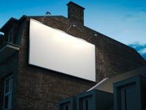Panneau d'affichage vide accrochant sur le bâtiment classique pendant la nuit Photo stock