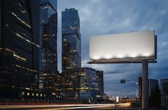 Panneau d'affichage vide au crépuscule à côté des gratte-ciel rendu 3d Photos stock