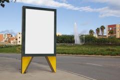 Panneau d'affichage vide dans une rue verte Images libres de droits