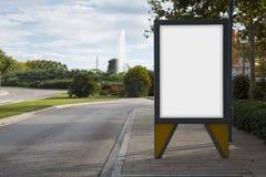 Panneau d'affichage vide dans une rue verte Image libre de droits