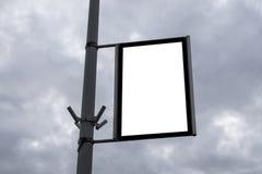 Panneau d'affichage vide sur un poteau de réverbère contre des nuages Photographie stock