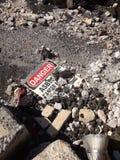 Panneau d'avertissement d'amiante s'étendant parmi des débris d'amiante Image stock