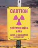Panneau d'avertissement de région de contamination avec le lever de soleil Photographie stock