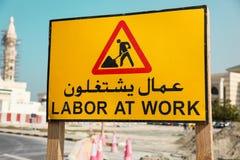 Panneau d'avertissement de route - travaillez au travail écrit sur un Arabe et un anglais Photos stock