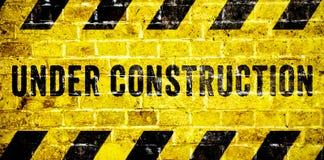 Panneau d'avertissement en construction avec les rayures jaunes et noires sur le fond de texture de mur de briques dans le format images stock