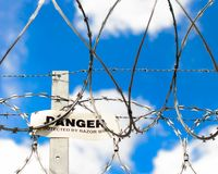 Panneau d'avertissement et barbelé photographie stock libre de droits