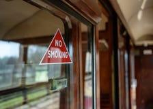 Panneau d'avertissement non-fumeurs vu attaché à un compartiment ferroviaire de première classe photographie stock