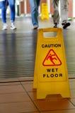 Panneau d'avertissement pour le plancher glissant avec des jambes de personnes dans le backgrou Photographie stock libre de droits