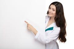 Panneau de carte vierge de prise de sourire de femme de médecin Image stock