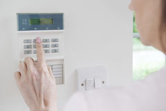 Panneau de commande d'arrangement de femme sur le système de sécurité à la maison Photographie stock