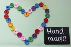 Panneau de craie avec le ` fait main de ` d'inscription entouré par un coeur des boutons colorés sur un fond clair Image stock