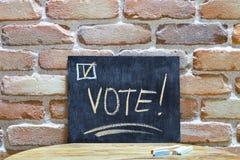 Panneau de craie avec le mot VOTE ! noyez-vous ? la main et marquez ? la craie sur la table en bois sur le fond de mur de briques image stock