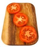 Panneau de découpage avec des parts de tomate Images stock