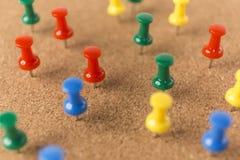 Panneau de liège avec le sort goupilles colorées Image stock
