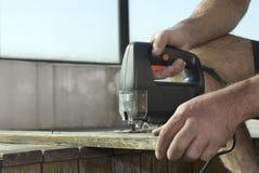 Panneau de Sawing d'homme avec la scie sauteuse - horizontale Images stock