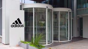 Panneau de signage de rue avec l'inscription et le logo d'Adidas Immeuble de bureaux moderne Rendu 3D éditorial Photo libre de droits