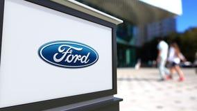 Panneau de signage de rue avec le logo de Ford Motor Company Centre brouillé de bureau et fond de marche de personnes 3D éditoria Photographie stock libre de droits