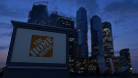 Panneau de signage de rue avec le logo de Home Depot le soir Fond brouillé de gratte-ciel de district des affaires banque de vidéos