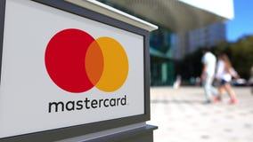 Panneau de signage de rue avec le logo de MasterCard Centre brouillé de bureau et fond de marche de personnes Rendu 3D éditorial Photo libre de droits