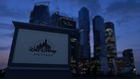 Panneau de signage de rue avec le logo de Walt Disney Pictures le soir Fond brouillé de gratte-ciel de district des affaires illustration stock