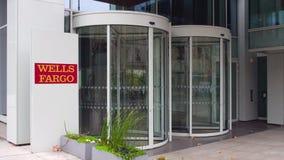 Panneau de signage de rue avec le logo de Wells Fargo Immeuble de bureaux moderne Rendu 3D éditorial Image stock
