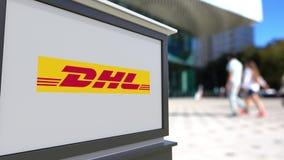 Panneau de signage de rue avec le logo exprès de DHL Centre brouillé de bureau et fond de marche de personnes Rendu 3D éditorial Images libres de droits