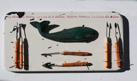 Panneau en bois avec une baleine et une collection d'hameçons et d'harpons Image stock