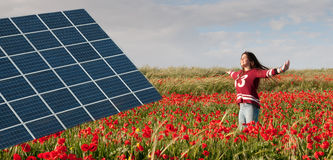 Panneau et adolescente à énergie solaire sur un champ avec les pavots rouges Images stock