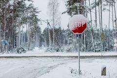Panneau routier à côté d'un chemin forestier couvert de neige Un chemin forestier et connexion une robe longue d'hiver Photographie stock libre de droits