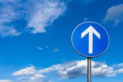 Panneau routier bleu avec avec la flèche se dirigeant au ciel bleu Image stock