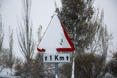 Panneau routier couvert de neige en hiver Photos stock