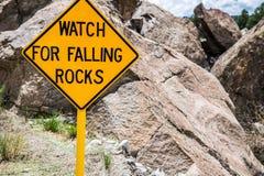 Panneau routier d'avertissement en baisse de danger de roches Photo stock