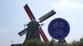 Panneau routier de bicyclette et grand moulin à vent néerlandais traditionnel sur le fond dans des schans de Zaanse, Pays-Bas banque de vidéos